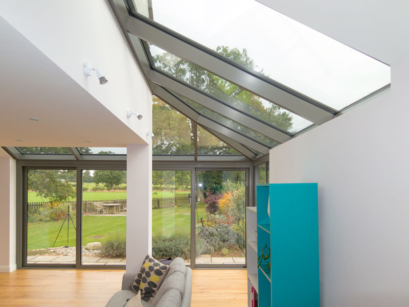 The aluminium roof stretches over the house wall, helping to integrate the roof with room.